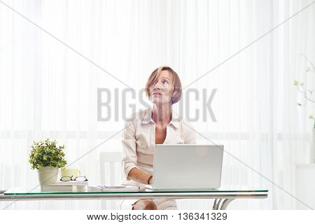Mature woman thinking over ideas for her blog post