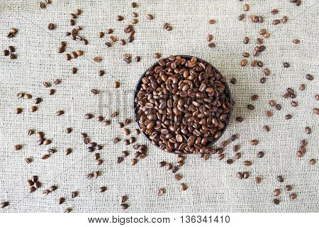 Burlap texture with coffee crop in a bowl background, plenty of robusta beans in plate closeup. Sack cloth canvas with copy space. Scattered seeds at hessian textile