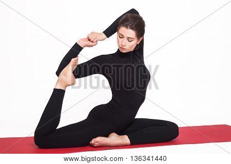 Beautiful athletic girl in a black suit doing yoga. eka pada rajakapotasana asana - pigeon pose royal. Isolated on white background.