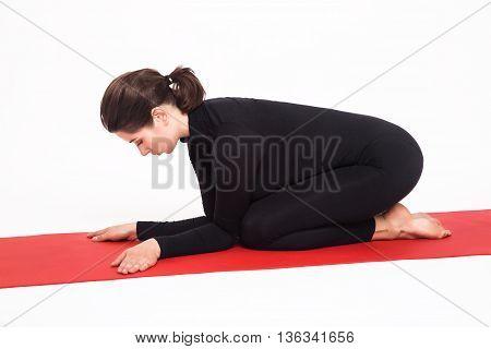 Beautiful athletic girl in a black suit doing yoga. karenukasana asana - pose lying elephant . Isolated on white background.