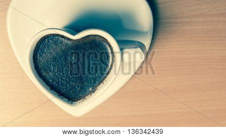 Hot coffee beverage in heart shaped cup mug on wooden board. Caffeine energy. Cross filtered.
