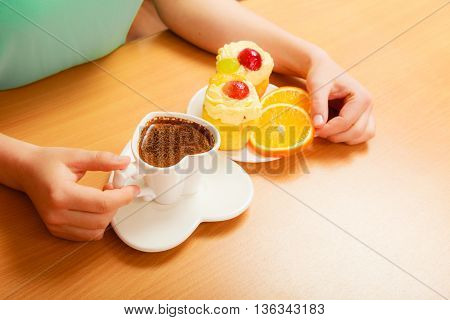 Woman taking gourmet tasty cookie cake with sweet cream and fruits as dessert food on top served with orange on plate. Hot coffee beverage.