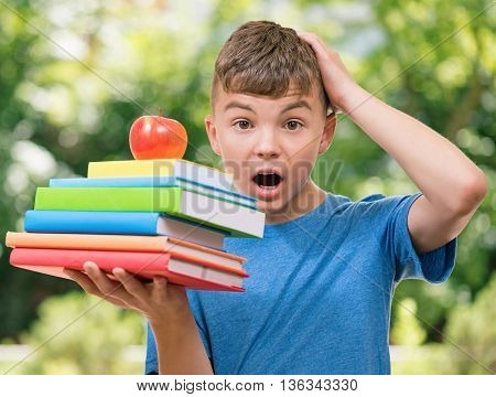 Shocked teen boy 12-14 year old with books posing outdoors
