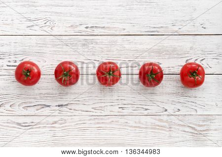 Five red tomatoes in a row on a white wooden background. Copy space. Artistic still life