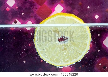 Slice of yellow lemon partially lowered into the water with bubbles on a purple background on an abstract