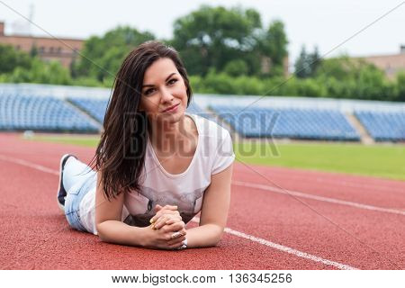 Portrait of a beautiful brunette woman lying on a treadmill at the stadium