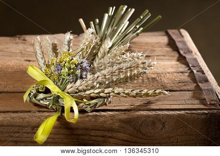 bundle of wheat with flower and band ojn the wooden desk