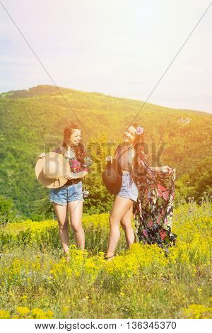 Two beautiful young boho sisters in floral print and denim, outdoors on sunny summer day in nature. Two happy hippie friends having fun in nature. Medium retouch, vibrant colors.