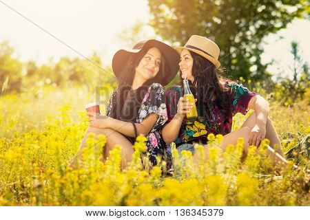 Two happy young boho hippie sisters drinking juice and coffee outdoors on sunny summer day, sitting in meadow. Medium retouch, vibrant colors.