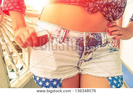 Young woman phone in denim shorts pocket - Beautiful pin-up girl body with hand holding cell inside summer season clothes - Concept of beauty and trendy clothing -