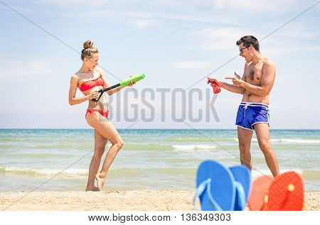 Playful young couple having fun on the beach - Sexy girl with water gun ready for summer holiday games - Concept of childish joyful moment and popular teenage activities at summertime