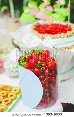 Candy bar for a children's holiday. Cake, candy, sweets and strawberries on a festive table