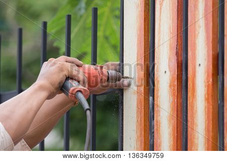 Hands Using Electric Drill On Fence Wood