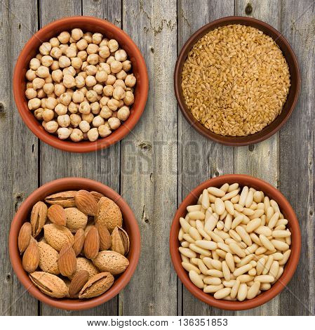 Seed super food selection in bowls on a wooden background. Chick-pea, linen, almond and pine nuts.