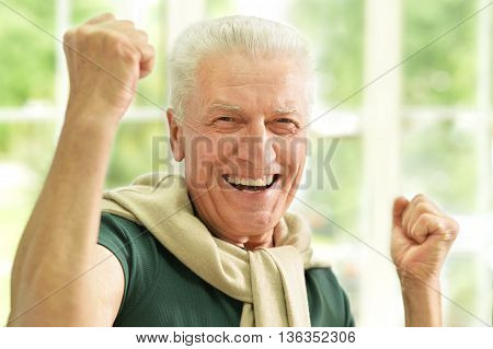 happy Senior man  at home with hands up