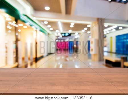 Wooden board empty table in front of blurred background. Perspective dark wood table over blur in shopping mall hall. Mock up for display or montage your product.