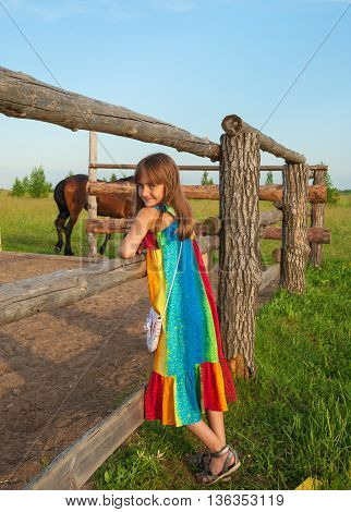 Beautiful little girl in a bright sundress standing near a wooden fence