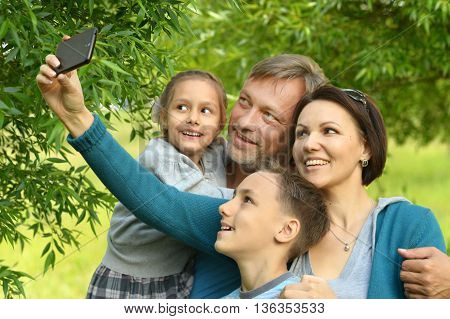 Portrait of a happy family taking selfie in park