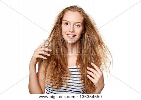 Beautiful natural young woman with flying hair touching her hair, over wgite background