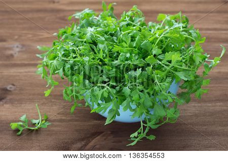 Fresh watercress in a blue bowl on a wooden table, selective focus