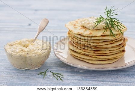 Flat bread with egg dip and dill on a blue wooden background, selective focus