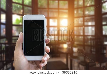 Man's hand shows mobile smartphone in vertical position and blurred background You can use this smartphone with blank screen for your smartphone application presentation - smartphone mockup template