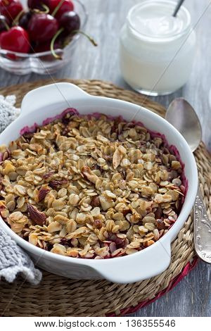 Homemade cherry crumble with oatmeal and almonds with fresh cherry and yogurt on a light wooden table