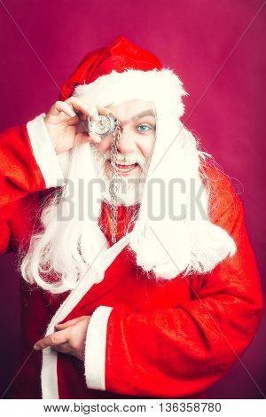 New year man with smiling face has long white beard and hair in red santa claus christmas coat and hat holding clock on chain on studio background