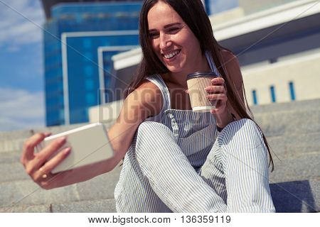 Portrait of slim beautiful lady who is making a selfie on city stairs with a cup of coffee to go in her hands
