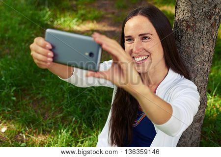 Smiling beautiful lady is resting under tree and making a selfie in the park