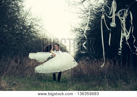 Beautiful bridal couple of young man and happy pretty woman walking outdoor near decorative ribbons