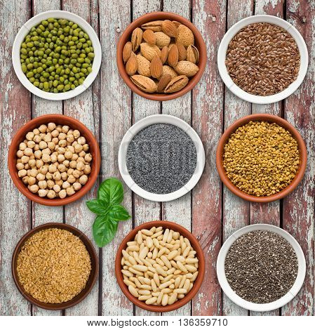 Large seed super food selection in bowls on a wooden background. Chia seeds, flax, chickpeas, poppy, almonds, pine nuts.