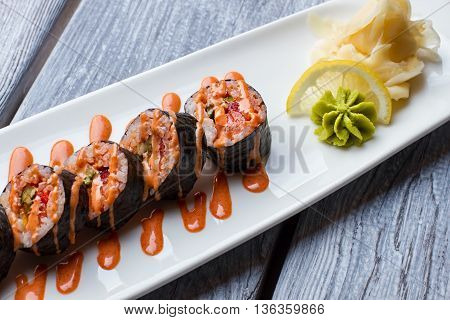 Sushi rolls on white plate. Wasabi and lemon beside sushi. Best dish in sushi cafe. Futomaki rolls served with spices.