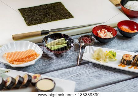Raw fish and sliced avocado. Small bowl with red caviar. Sushi ingredients on wooden table. Chef's table in japanese restaurant.