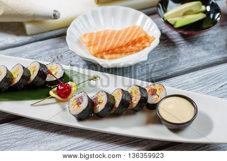 Bowl with sauce beside sushi. Sushi rolls and sliced fish. Decorated plate with futomaki rolls. Proven recipe from japanese cuisine.