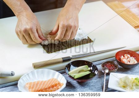 Hands touch white rice. Knife beside nori leaf. Basic ingredients for uramaki rolls. Original recipe of sushi.