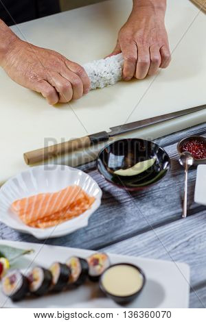 Man's hand touches sushi roll. Knife beside piece of avocado. Chef demonstrates the new recipe. Secrets of Japanese cuisine.