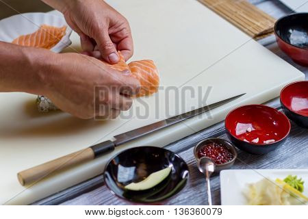 Man's hands over sushi roll. Pieces of raw fish meat. Fresh salmon for uramaki rolls. Japanese chef prepares traditional dish.