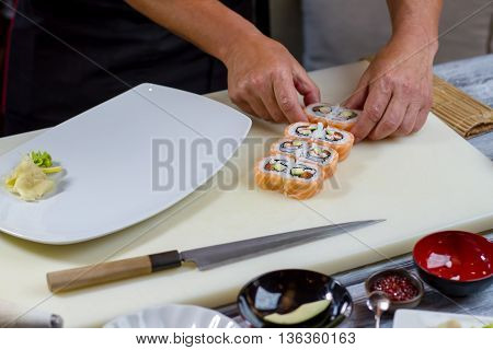 Man's hands touch sushi rolls. White plate on cooking board. Uramaki rolls prepared by cook. Favorite dish of gourmets.