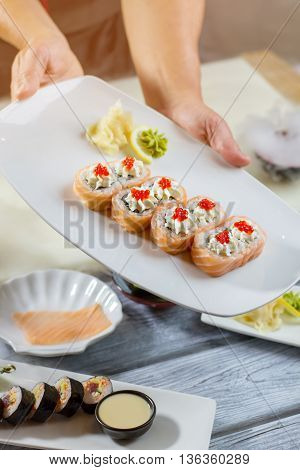 Man's hands hold sushi plate. Wasabi on lemon slice. Traditional uramaki rolls with caviar. Japanese dish for breakfast.