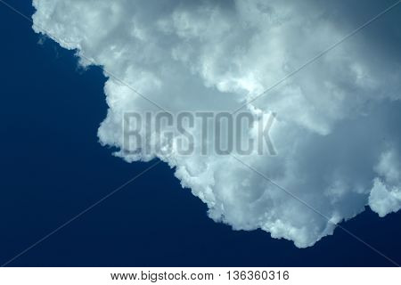 Big white fluffy cloud on blue sky background copy space