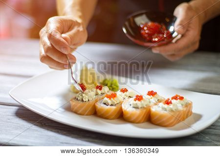 Spoon with caviar over sushi. Man's hand holding small spoon. Cream cheese and salmon caviar. Best recipe of uramaki rolls.