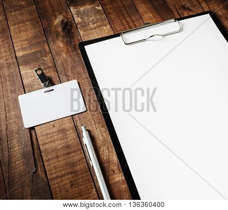 Close-up of blank letterhead in clipboard badge and pen on wooden table background. Blank template for your design. Responsive design mock-up.