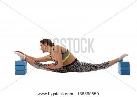 Image of woman doing stretching using gymnastic bricks