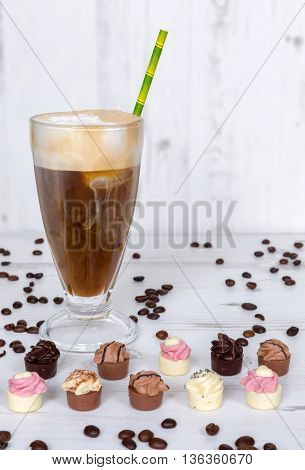 Ice Coffee with small pralines on white, vintage surface