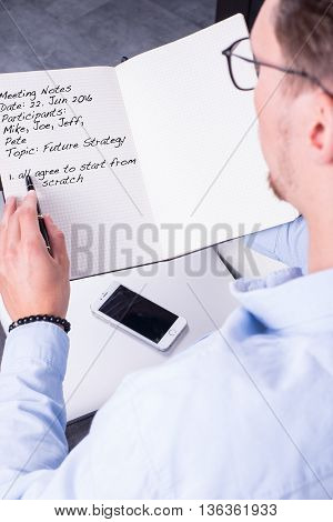 young man is taking meeting notes in open notebook