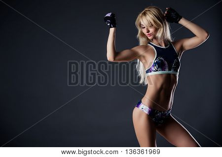 sporty woman is showing her strong hands on grey background.