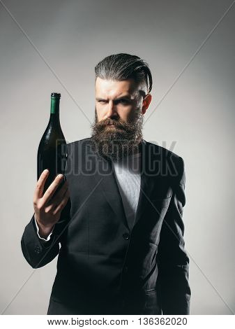 Handsome young man with long beard and moustache in black jacket holding green glass wine bottle in studio on grey background