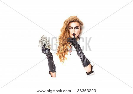 Pretty woman with long lush curly hair holding money in hands with black leather gloves in torn paper isolated on white background