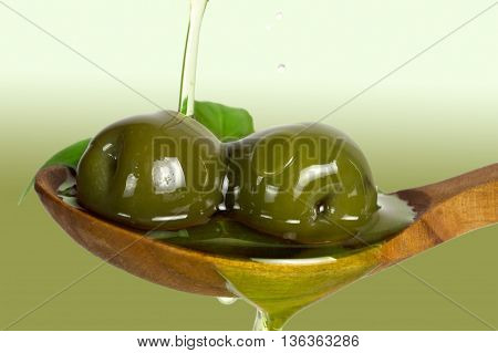 Fresh green olives over spoon. Olive oil poured on olives.